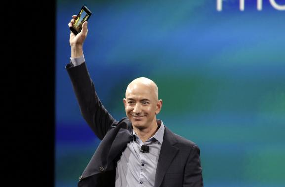 1 OF 3. Amazon CEO Jeff Bezos shows off his company's new smartphone, the Fire Phone, at a news conference in Seattle, Washington June 18, 2014. CREDIT: REUTERS/JASON REDMOND