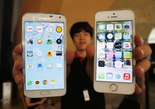 A sales assistant holding Samsung Electronics' Galaxy 5 smartphone (L) and Apple Inc's iPhone 5 smartphone (R) poses for photographs at a store in Seoul July 16, 2014. CREDIT: REUTERS/KIM HONG-JI